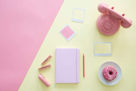 Pastel pink and yellow color trends top view duotone composition of everyday objects - a notebook, vintage phone, doughnut and mock-up space