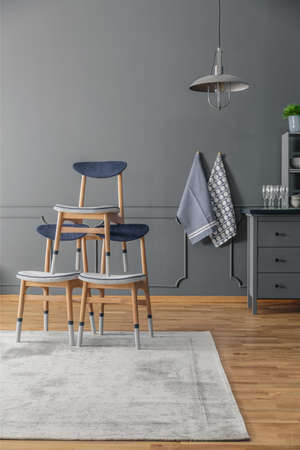 Chairs standing on a rug in a kitchen interior with wooden floor and grey walls Stock Photo