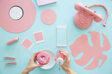 View from above on female hands holding a pink smoothie and doughnut on a pale blue background with rose quartz conceptual objects Stock Photo