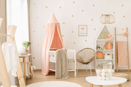 Sweet, spacious nursery room interior for a baby girl with white furniture, pastel pink decorations and golden polka dot wallpaper