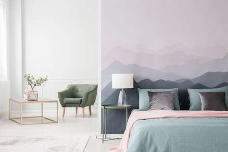 Large bed with blue sheets and a pink blanket by a landscape wallpaper in a cozy, modern bedroom interior