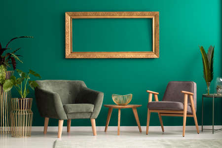 Elegant fruit bowl on a wooden table between retro armchairs with wooden legs in a luxurious, green living room interior with plants