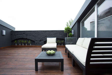 Wooden table and white garden furniture on terrace with black brick wall and view on the sky Stock Photo