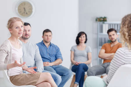 Female therapist discussing problems with her patients during an AA support group meeting Stock Photo - 97946739