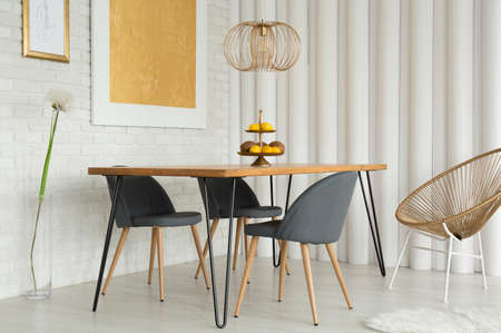 Gold chair next to table under lamp in modern dining room interior with painting and dandelion Imagens