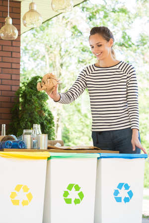 Eco friendly woman segregating waste on a terrace with yellow, green and blue bin Stockfoto