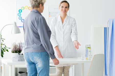 Smiling doctor in white uniform welcoming her patient in the office