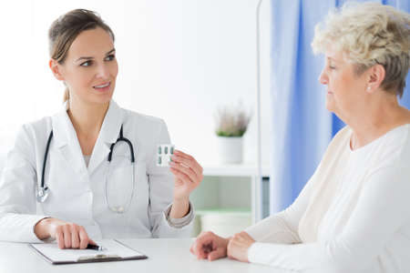 Doctor with stethoscope giving pills for headache to a patient during consultation in the office Stock Photo