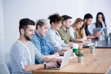 Young man working on his laptop by a table in the foreground and blurred coworkers collaborating in a meeting Stock Photo