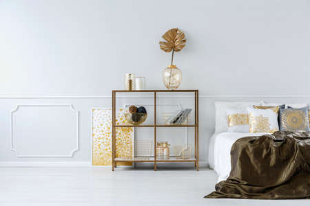 Gold leaf in vase on a shelf against white molding wall in sophisticated bedroom interior with bed Stock Photo