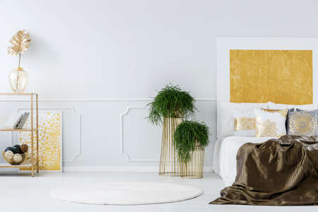 Plants next to a dark bed against white wall with gold painting in elegant bedroom interior