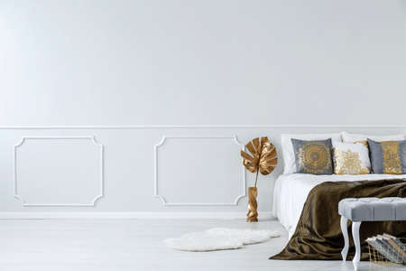 Gold leaf next to bed in modern bedroom interior with copy space on white wall with molding