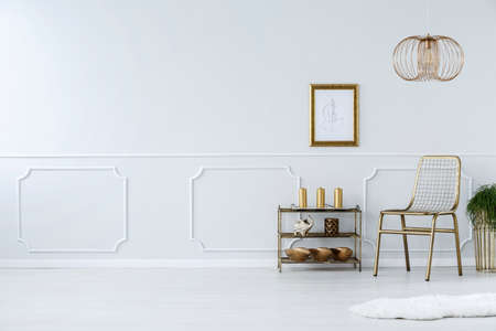 Gold chair against white wall with molding in living room interior with poster and copy space