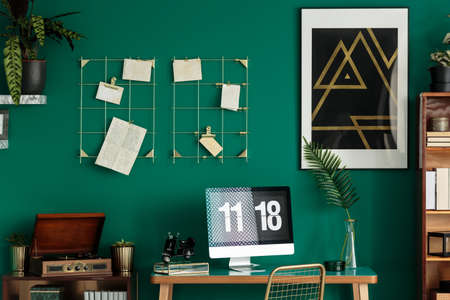 Wooden phonograph, computer on a desk and black poster on a green wall in home office interior
