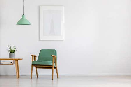 Poltrona retrò, come nuova, tavolo in legno e poster incorniciato in un luminoso interno minimalista con spazio di copia
