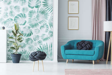 Stylish living room interior with a creative knot pillow stool, turquoise sofa, plant and a wallpaper with leaves
