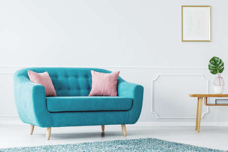 Turquoise sofa and pink cushions on a white, wooden floor of a minimalist design living room interior with white wall with copy space