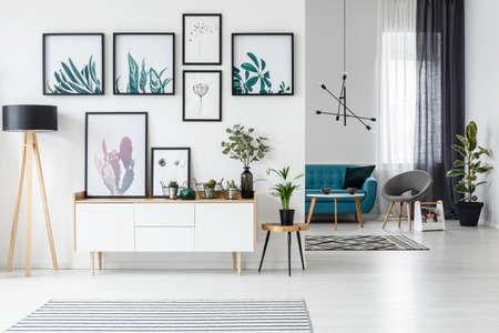 Białe wnętrze salonu z plakatami botanicznymi na ścianie i sofą w tle Zdjęcie Seryjne