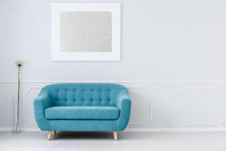 Canapé bleu à l'intérieur de la salle d'attente blanche avec moulure murale, fleur et peinture