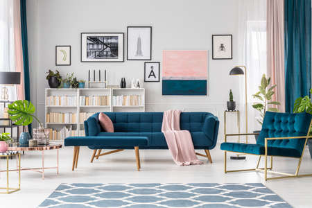 Blue living room interior with sofa, bookshelf and art collection