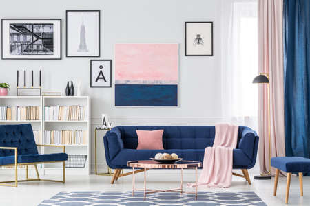White, blue and pink living room interior with couch, paintings and curtains Stockfoto