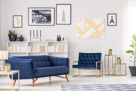 Art collection, white bookshelf, blue sofa and armchair in modern living room interior