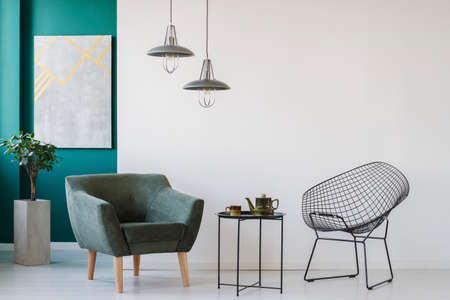 Metal coffee table between armchairs against an empty wall in living room interior with modern lamps Stock Photo