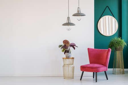 Pflanzen Sie auf goldenem Tisch neben einem rosa Sessel auf einer weißen, leeren Wand im Lobby-Interieur