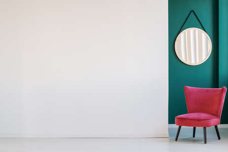 White, empty wall, round mirror and pink armchair in a corridor interior