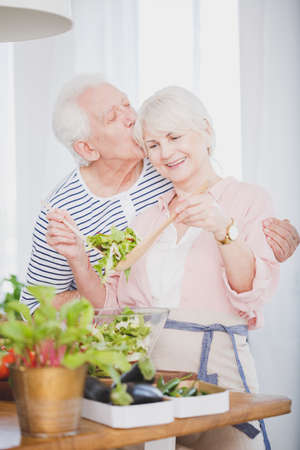 Senior couple cooking dinner in the kitchen, kissing each other and smiling Stockfoto