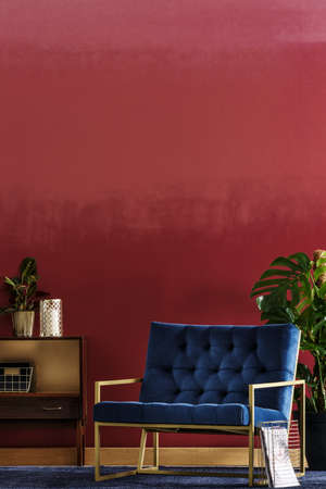 Blue armchair set on a red, ombre wall between a plant and wooden cupboard in living room interior 版權商用圖片