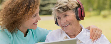 Close-up of a smiling old lady wearing headphones, with her nurse