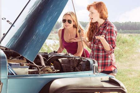車の故障に出くわす2人の若い女の子 写真素材