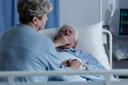 Elderly man with lung cancer lying in a hospital bed and coughing Stock fotó - 99321578