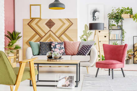 Green and red armchair near sofa with patterned pillows in botanic living room interior