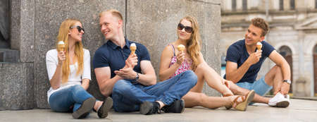 Group of smiling friends eating ice cream at the foot of a monument