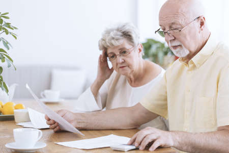 Sad elderly marriage sitting with documents and calculator at a table with coffee
