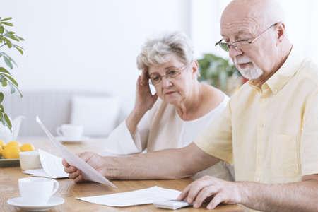 Smutne małżeństwo w podeszłym wieku siedzi z dokumentami i kalkulatorem przy stole z kawą