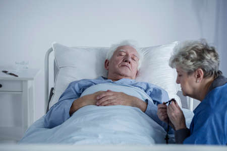Elderly woman sitting next to her terminally ill husband and praying with a rosary in a hospital Stock fotó - 99321817