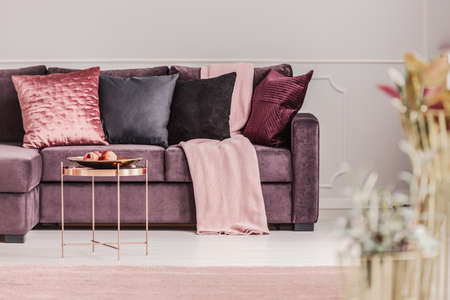 Copper table next to a violet sofa with decorative cushions in pink womans living room interior