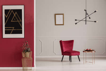 Gold table against red wall with black poster in apartment interior with armchair against white wall Foto de archivo
