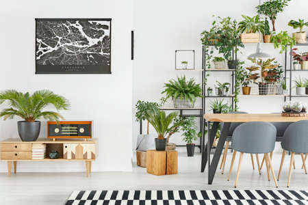 Black map on the wall above wooden cupboard with radio in dining room interior with plants 스톡 콘텐츠