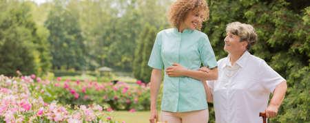Ltere Frau mit einem Stock, gehend mit ihrer Krankenschwester im Garten Standard-Bild - 99321990
