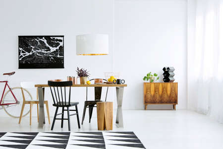 Patterned carpet, wooden table with chairs and cupboard in dining room interior