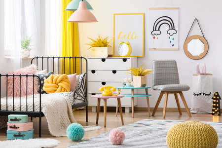 Yellow pouf and grey chair in colorful kids bedroom interior with poster on the wall