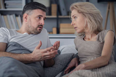 Couple lying in bed and talking about theirs problems in relationship