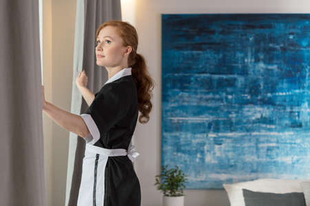 Maid unveiling curtains in a hotel room with blue painting on the wall