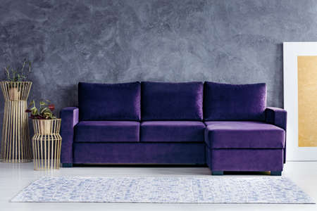 Velvet corner sofa next to gold pots in glamour living room interior with concrete wall Stock Photo