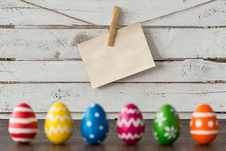 Mockup of paper note pinned with a clip against planks. Easter card Stock Photo