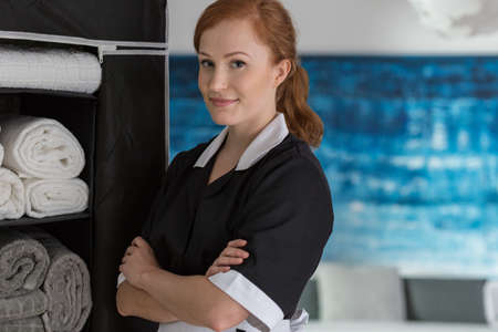 Smiling maid in a black and white uniform in a hotel room next to a wardrobe Zdjęcie Seryjne - 98254704